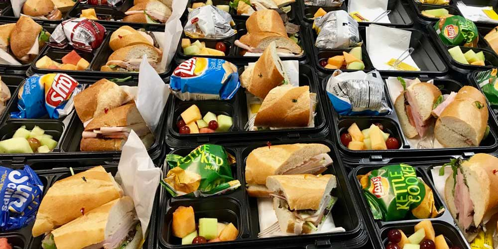 Box lunch buffet service with sandwiches, chips and salad prepared and ready for Rise & Shine corporate client event
