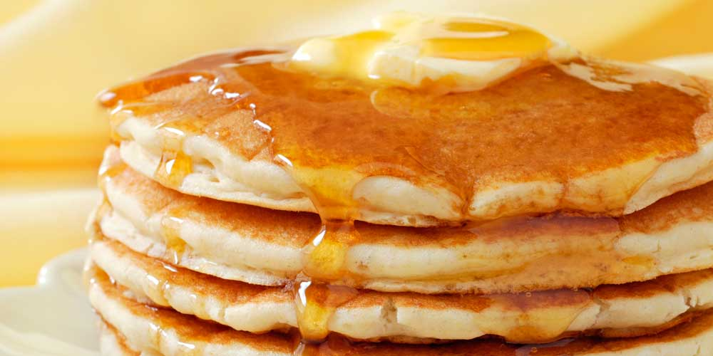 Stack of pancakes with butter and syrup as part of Rise & Shine's breakfast catering service